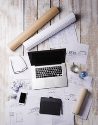 Desk of an architect with laptop and blue prints - HAPF000375