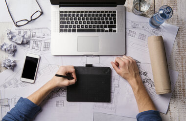 Architect working at desk with laptop, making sketches - HAPF000378