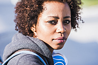 Portrait of young woman wearing headphones outdoors - UUF007242