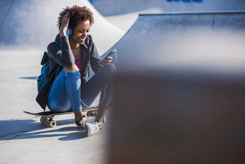 Smiling young woman sitting on skateboard listening to music - UUF007248