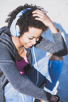 Smiling young woman wearing headphones outdoors - UUF007251