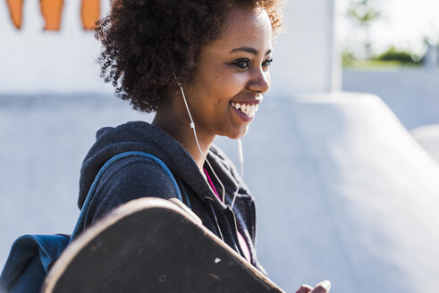 Smiling young woman with skateboard listening to music - UUF007260