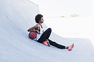 Young woman sitting with basketball outdoors - UUF007269