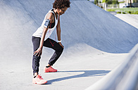 Young woman stretching in skatepark - UUF007281