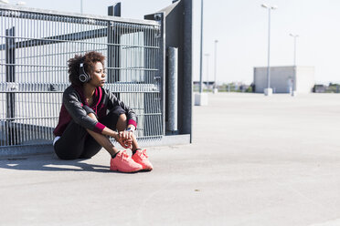 Young woman wearing headphones on parking lot - UUF007299