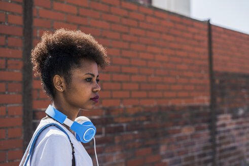 Young woman wearing headphones in front of brick wall - UUF007305