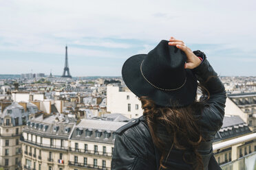 France, Paris, back view of woman at viewpoint wearing a black hat - GEMF000905