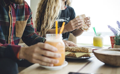 Couple having breakfast in cafe, drinking organic juices - DAPF000095
