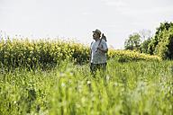 Farmer holding hoe at rape field - UUF007322