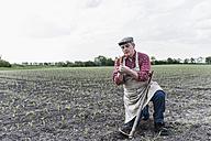 Farmer at a field examining crop - UUF007325