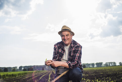 Portrait of smiling farmer in a field holding crop - UUF007343