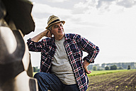 Farmer leaning on tractor at a field - UUF007349