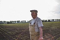 Smiling farmer standing at a field - UUF007352