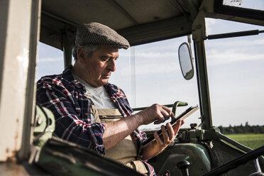 Farmer sitting in tractor using digital tablet - UUF007361