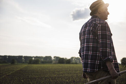 Farmer holding rake next to a field - UUF007367