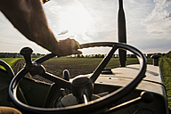 Close-up of farmer steering tractor next to field - UUF007370