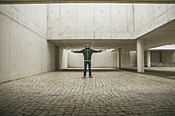 Man with arms outstretched and head back in modern architecture - ABZF000529