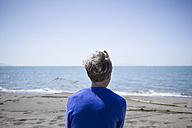 Back view of woman in front of the sea - RIBF000397