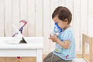 Girl using inhaler looking at digital tablet - DRF001710