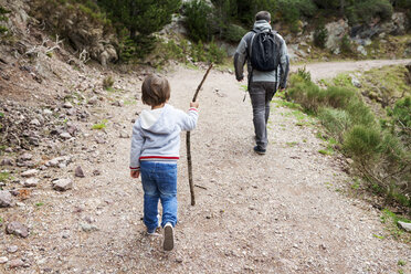 Father and son hiking on rural path - VABF000486