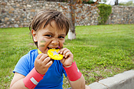 Little boy biting on medal - VABF000498