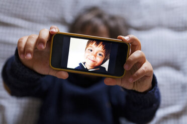 Little boy holding a cell phone with picture of himself - VABF000504