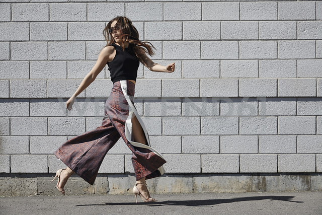 Fashionable young woman passing brick wall - MHCF000018 - Mateo H Casis/Westend61