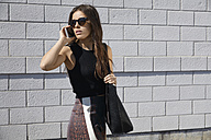 Fashionable young woman in front of brick wall on the phone - MHCF000021