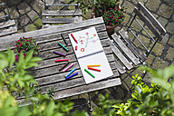 Drawing, sketch book with drawing and coloring pencils on wooden garden table - GWF004705