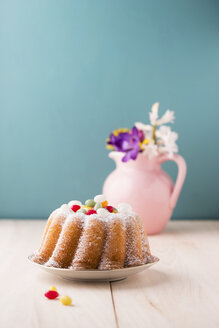 Ring cake with Easter eggs and bunch of flowers in the background - MYF001486