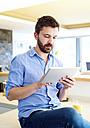 Man working in kitchen using digital tablet - HAPF000387