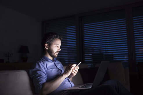 Man working at night using smart phone and laptop - HAPF000426