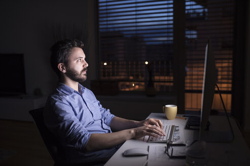 Man working at night, using computer - HAPF000429