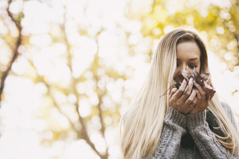 Teenage girl smelling autumn leaves - SELF000091