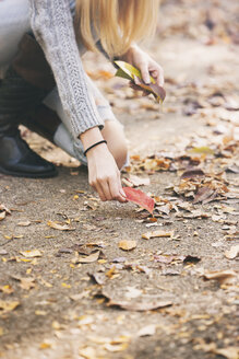 Teenage girl collecting autumn leaves - SELF000097