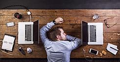Young man sleeping at work, power napping - HAPF000439