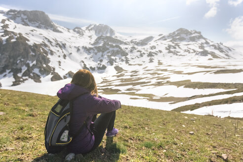 Spain, Asturias, Somiedo, woman looking at the landscape sitting in a meadow - MGOF001862