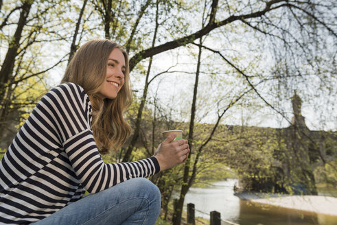 Smiling young woman outdoors with cup of coffee - KAF000142