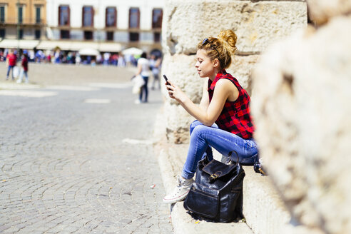 Italy, Verona, woman sitting on stairs looking at cell phone - GIOF001059