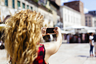 Italy, Verona, woman taking a cell phone picture in the city - GIOF001074