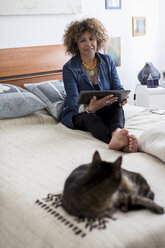 Woman with cat on bed holding digital tablet - MAUF000635