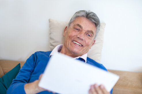 Smiling senior man lying on couch using digital tablet - DIGF000490