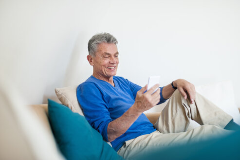 Smiling senior man sitting on couch using cell phone - DIGF000493