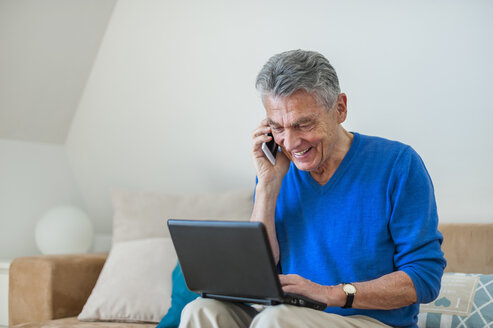 Smiling senior man sitting on couch using laptop and cell phone - DIGF000496