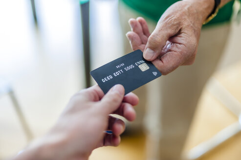 Close-up of two hands with credit card - DIGF000514