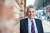 Portrait of confident senior businessman leaning against brick wall - DIGF000538