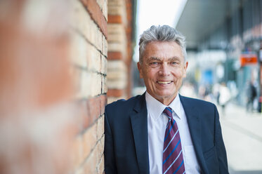 Portrait of confident senior businessman leaning against brick wall - DIGF000538