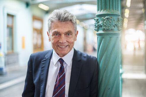 Portrait of confident senior businessman at column - DIGF000544