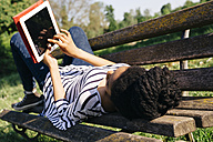 Young woman lying on park bench using digital tablet - GIOF001094