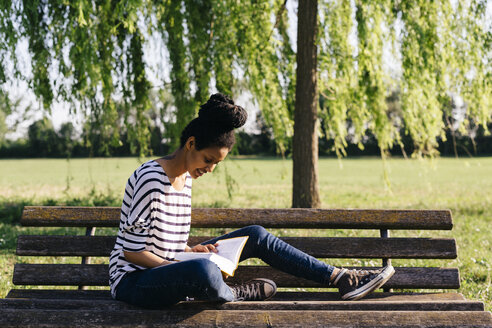 Young woman sitting on park bench reading a book - GIOF001097